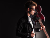 Cool young guitarist holding his electric guitar on shoulder Stock Photography