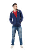 Cool young guy in blue sweatshirt with hands in pockets looking away. Full body length portrait isolated over white studio background Stock Images