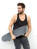 Cool young guy holding skate board Royalty Free Stock Images