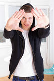 Cool young guy in hooded jacket framing his face with hands Royalty Free Stock Photos