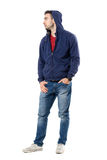 Cool young guy in hoodie with hands in pockets looking away. Full body length portrait isolated over white studio background Royalty Free Stock Photo