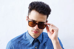 Cool young guy peeking over sunglasses Royalty Free Stock Photo
