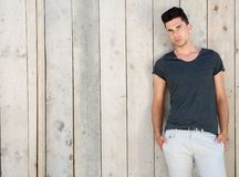 Cool young guy posing outside against wooden wall Royalty Free Stock Image