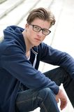 Cool young guy sitting outdoors. Close up portrait of a cool young guy sitting outdoors royalty free stock images