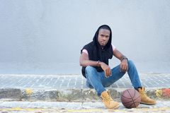 Cool young guy sitting on sidewalk with basketball Stock Images