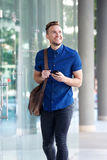 Cool young guy walking in city with cellphone Royalty Free Stock Images