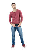 Cool young macho fashion male model posing and holding belt looking at camera. Full body length portrait isolated over white background Stock Photo