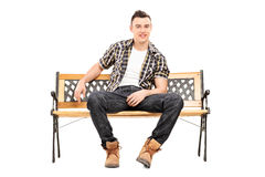Cool young male model sitting on a bench Stock Images