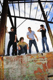 Cool young male teen in grunge urban. Portrait of young trendy group of men stading over grunge wall Stock Image