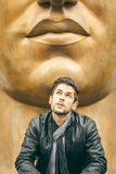 Cool young man. An image of a young man and a big mouth statue Royalty Free Stock Photo