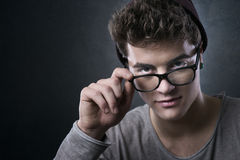 Cool young man adjusting his glasses. Cool young man adjusting his stylish glasses with flirty expression Stock Image