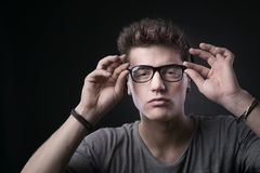 Cool young man adjusting his glasses Stock Photography