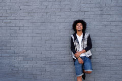 Cool young man with afro leaning against wall Royalty Free Stock Photos