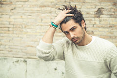 Cool young man fashion model, hairstyle. Hand in the hair Stock Image