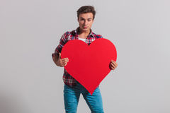 Cool young man holding a big red heart. On grey studio background Royalty Free Stock Photography