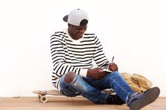 Cool young man sitting on skateboard outdoors and writing on book. Portrait of cool young man sitting on skateboard outdoors and writing on book Stock Photo