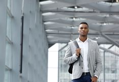 Cool young man walking inside station building with bag Royalty Free Stock Images