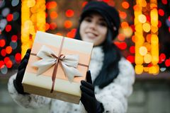 Cool young model wearing fur coat and cap pulls a gift box to yo royalty free stock image