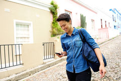 Cool young modern woman walking with cell phone and bag Royalty Free Stock Photography
