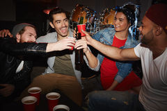 Cool Young People Cheering at Night Club Party. Group of smiling young party people drinking beer and raising glasses hanging out in night club on stage Royalty Free Stock Photography