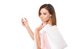 Cool young shopper using smartphone. Royalty Free Stock Image
