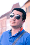 Cool young traveller with sunglasses. Portrait of a dark haired young man with American pilot sunglasses traveling. The blurry background is of an old medieval stock photos