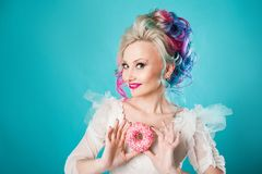 Cool young woman with colored hair and sweet donut, funny Stock Photo