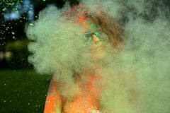Cool young model having fun in a cloud of green dry powder, celebrating Holi colors festival stock photography