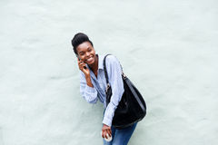 Cool young woman laughing with cell phone and bag Stock Photos