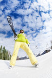 Cool young woman in mask standing and holding ski. During sunny winter day on Krasnaya polyana ski resort and Caucasus mountains in Sochi, Russia Royalty Free Stock Images