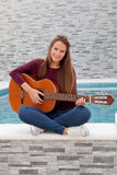 Cool young woman playing guitar Stock Photography