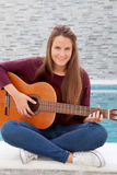 Cool young woman playing guitar Stock Images