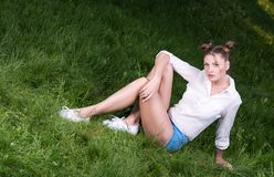 Cool young woman posing sitting on the grass. A modern, casual look. Short shorts and a white shirt. Hairstyle and light makeup Stock Image