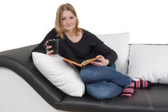 Cool young woman is reading a book on the couch Stock Photo