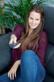Cool young woman sitting on the sofa with a remote control Stock Photography