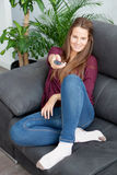 Cool young woman sitting on the sofa with a remote control Stock Image