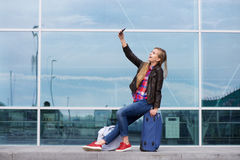 Cool young woman taking selfie with travel bags Royalty Free Stock Photography