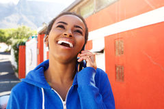 Cool young woman talking with cellphone against red wall Royalty Free Stock Image