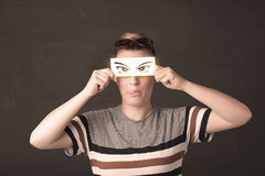 Cool youngster looking with a paper hand drawn eyes Royalty Free Stock Image