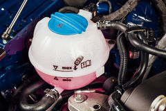 Coolant antifreeze tank under engine hood. Closeup view Royalty Free Stock Photography