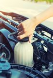 Coolant car check. Asian girl checking level of coolant car engine Stock Images