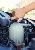 Coolant car check. Asian girl`s hand checking level of coolant car engine Stock Photo