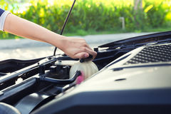 Coolant car check. Asian girl`s hand checking level of coolant car engine Stock Image