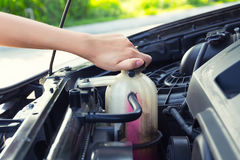 Coolant car check. Asian girl`s hand checking level of coolant car engine Royalty Free Stock Photo