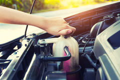 Coolant car check. Asian girl`s hand checking level of coolant car engine Royalty Free Stock Image