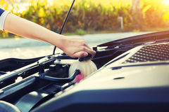 Coolant car check. Asian girl`s hand checking level of coolant car engine Stock Photos