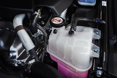 Coolant tank with a pink liquid antifreeze. Coolant tank with a pink liquid antifreeze of a radiator system in car stock image