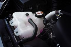 Coolant tank with a pink liquid antifreeze. Coolant tank with a pink liquid antifreeze of a radiator system in car, automotive part concept stock images