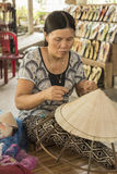 Coolie hat manufacture. A lady making a Coolie hat in a shop near Hue in Central Vietnam. This was one of the ladies who worked/owned the road side shop/ stock image