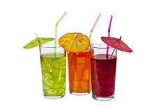 Cooling Drinks. Three Glasses of refreshing iced drinks, with straws and Parasols. Isolated on white Royalty Free Stock Images